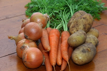 44143206 - a selection of root vegetables onions, carrots and potatoes on a wooden kitchen table