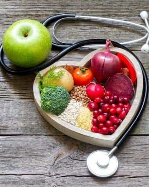 healthy food in a heart shaped bowl with a stethescope wrapped around it