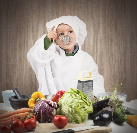 Kid Cooking with fresh produce in front of him.