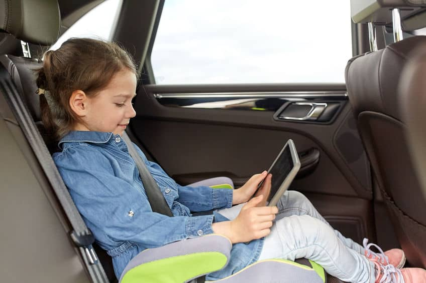 a young girl is reading her tablet while riding in the car.
