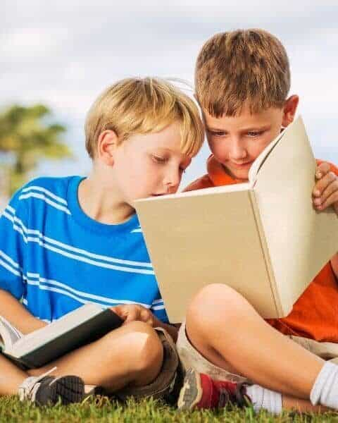 two boys reading books together