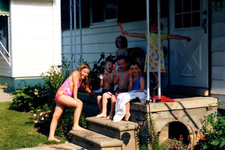 Group of children sitting on the front porch eating Popsicle