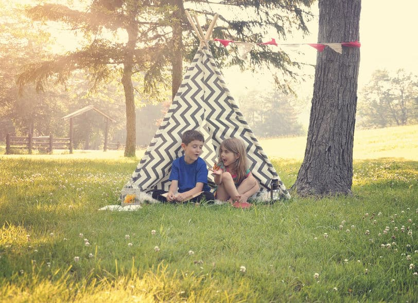 Two children outside playing in a tent.