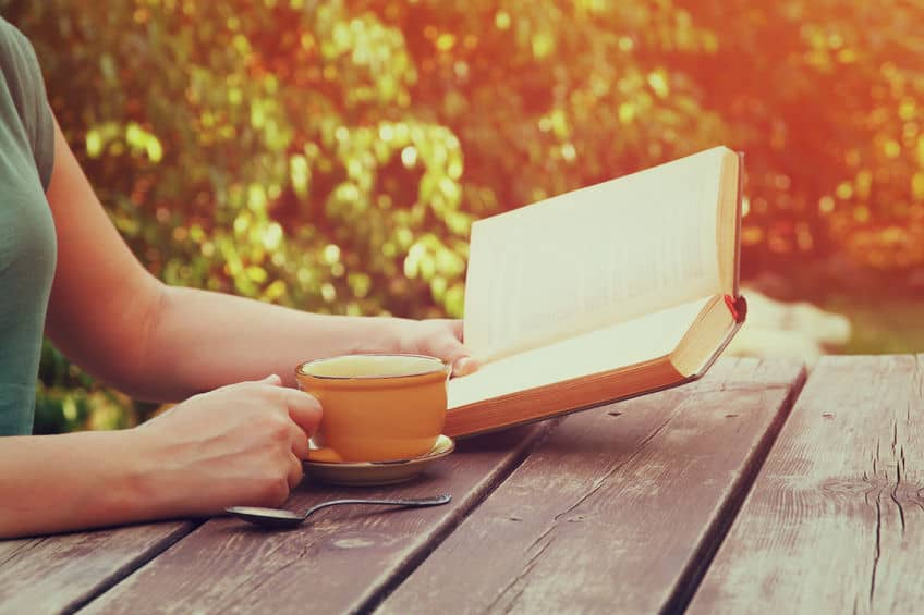 A woman sitting on a park bench with a cup of her favorite drink and a good book.