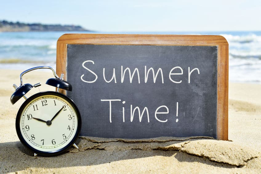 """A clock by a sign that reads, """"Summer time!"""" on the beach."""