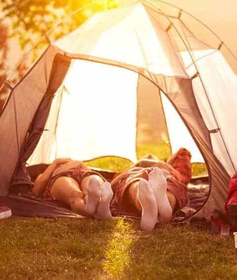 A couple laying down inside a tent with the flaps open. How to plan an awesome staycation for your family.