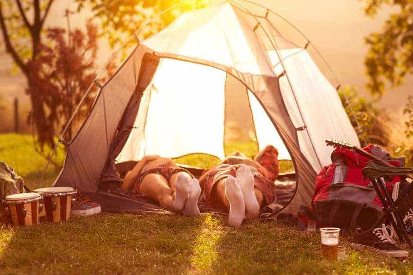 A couple camping in a tent.