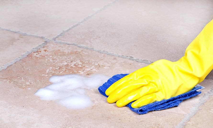 Scrubbing the dirty floor by hand with soap and water.