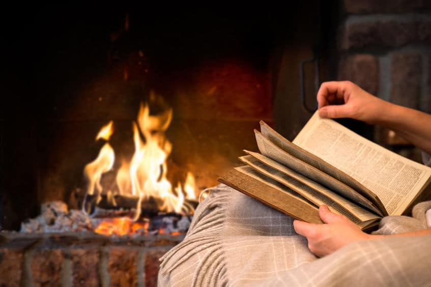 Reading book by a cozy fire.