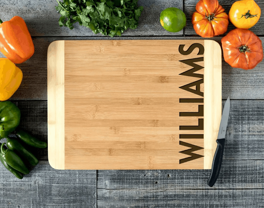 A green apple on top of a wooden cutting board, with Bamboo Cutting Boards and Kitchen
