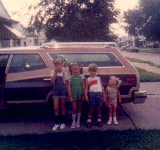 A family of children standing in front of an old car.