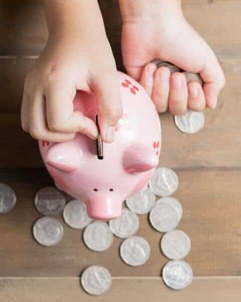 kid putting change into a pink piggy bank