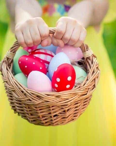 girl holding a basket filled with Easter eggs