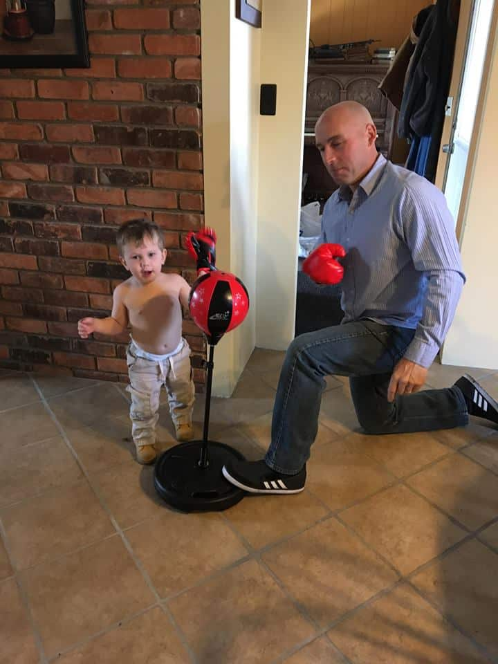 A man with his grandson boxing and hitting a punching bag.