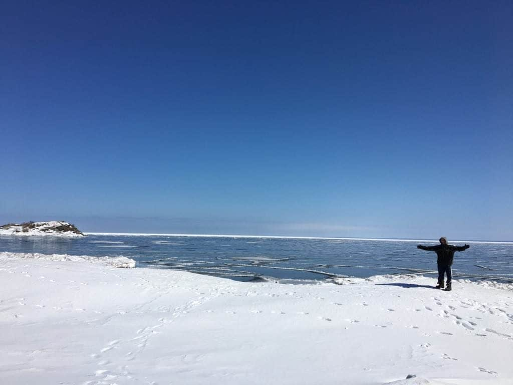 A man holding a snow board on a body of water