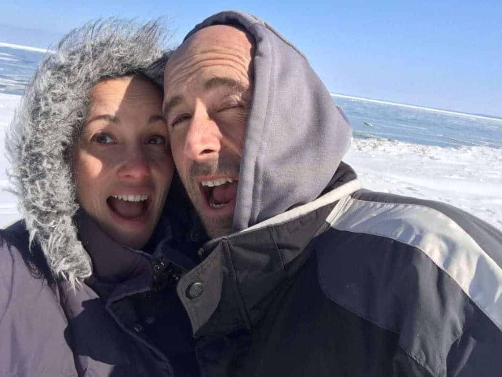 A couple posing and smiling on the beach in the middle of winter.