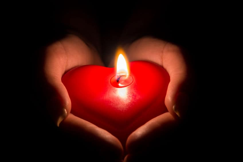 Heart shaped candle burning.