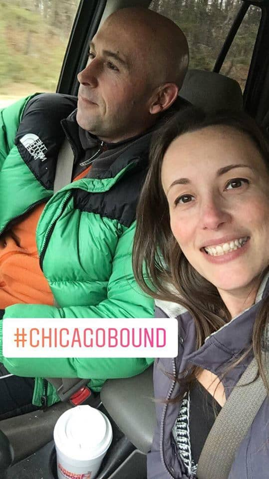 A couple of people posing for the camera heading to Chicago.