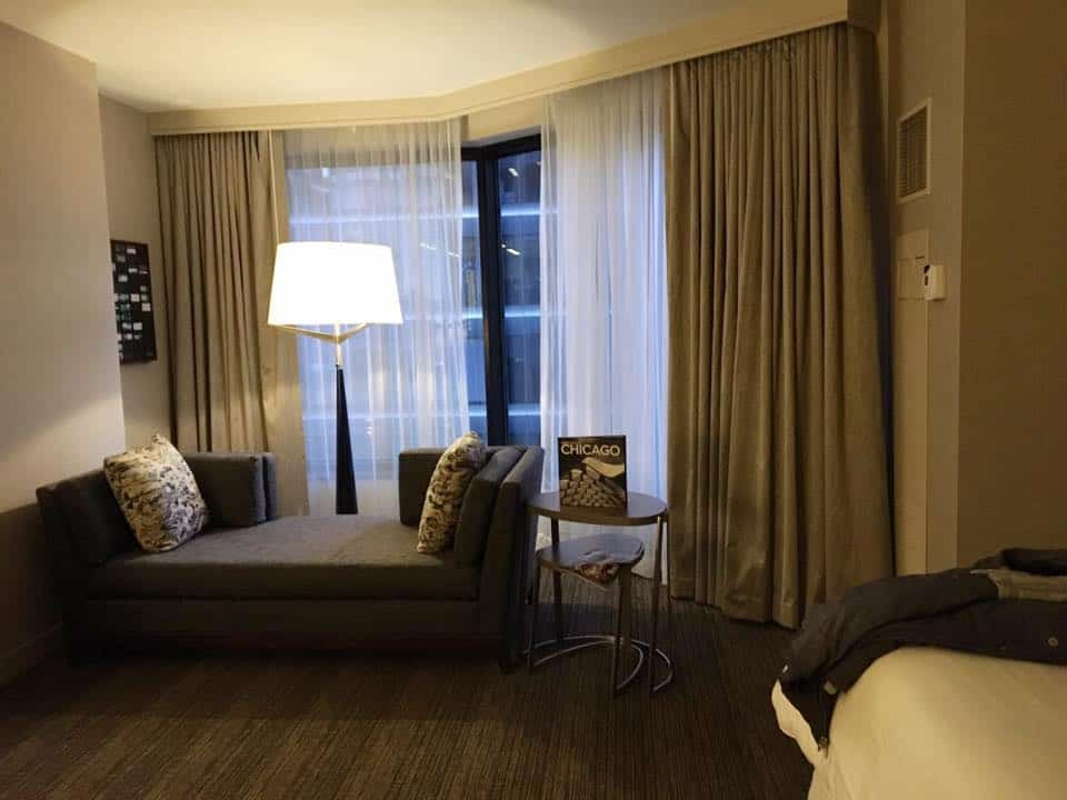 A hotel room in Chicago with a bed and looking at the camera