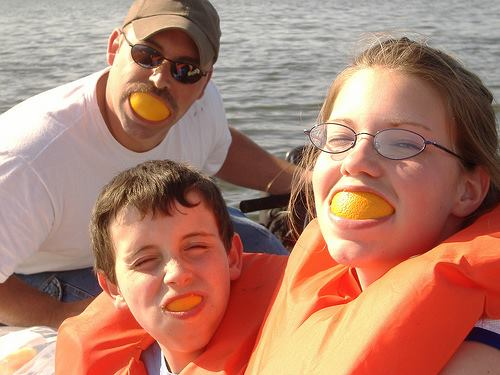 Orange slices in mouth of family members.