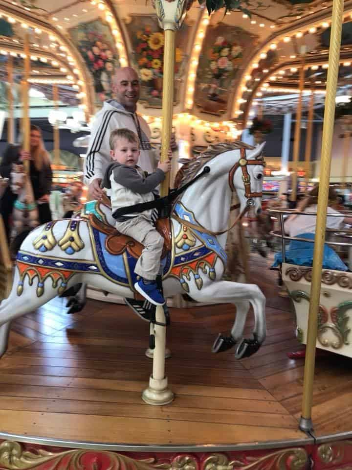 A person riding on the back of a carousel