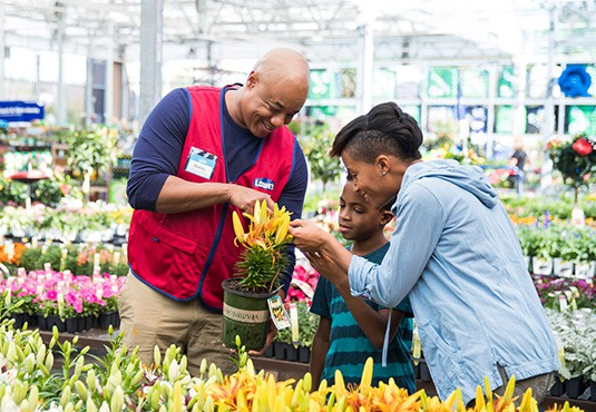 A Lowes employee standing in front of a flower helping a family of customers.