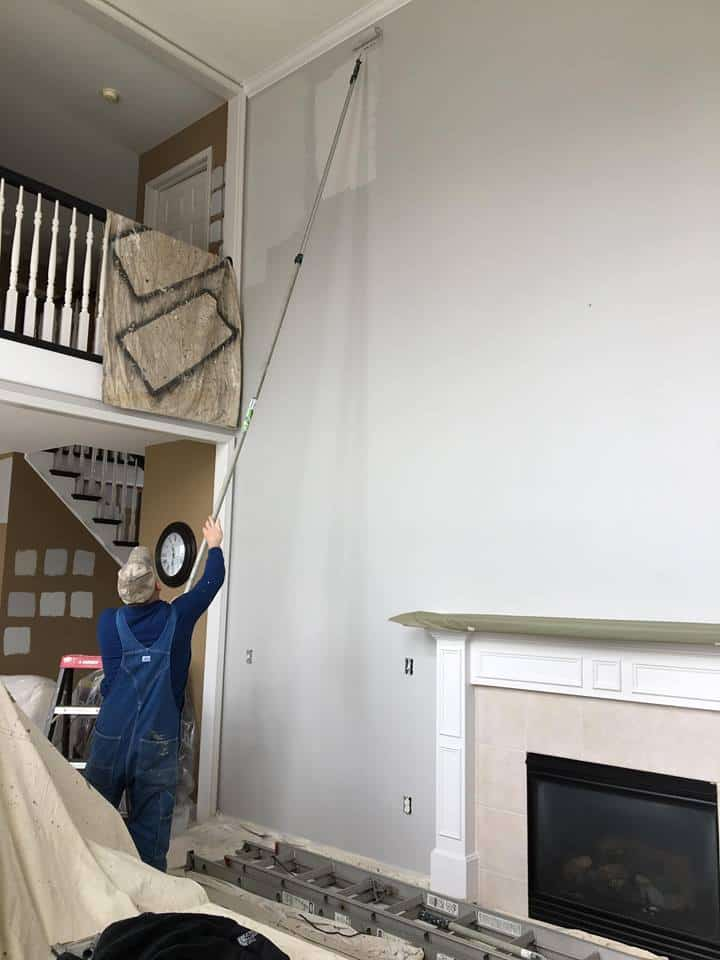 A person in the middle of their living room painting their tall wall.