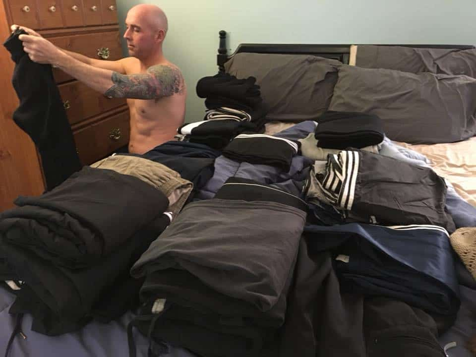 A man sitting on a bed with piles of clothes on the bed.