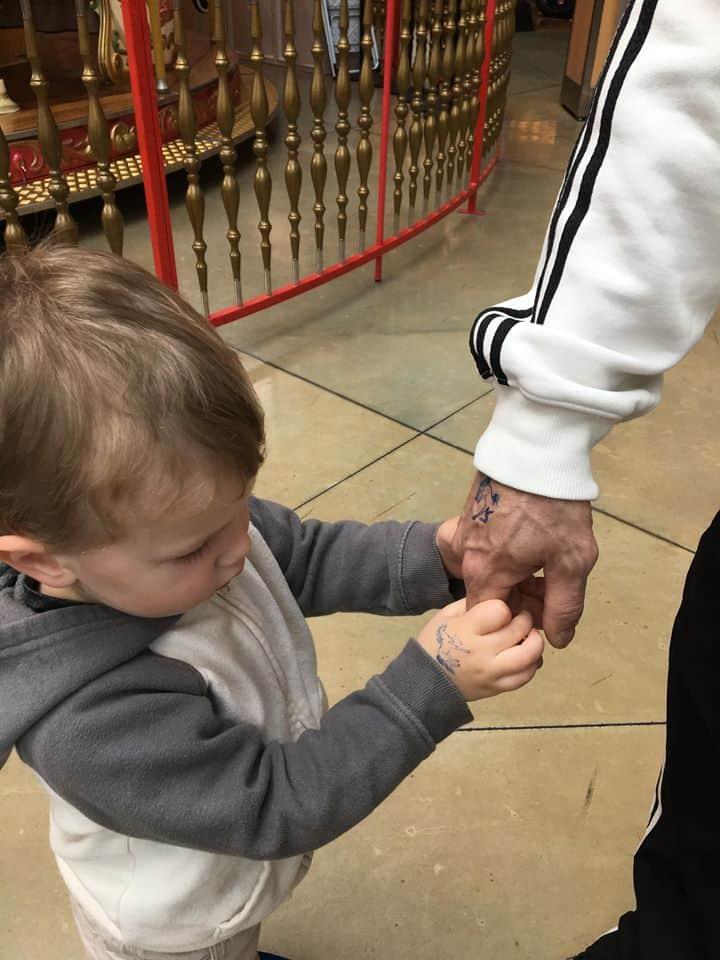 Little boy holding grandpa\'s hand.