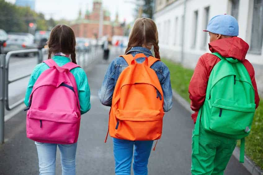 school age kids with backpacks