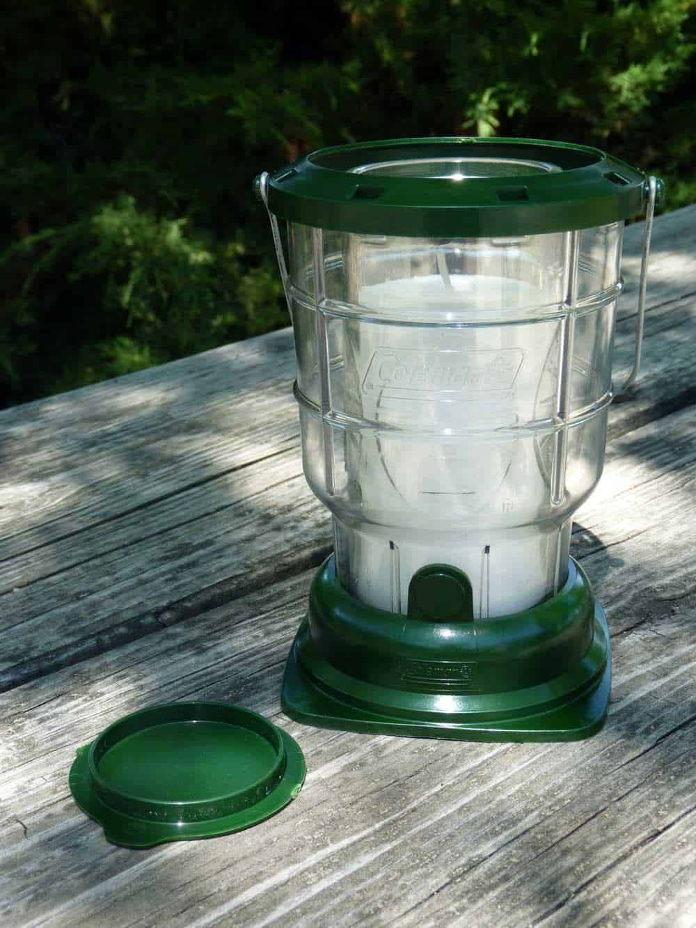 Coleman lantern sitting on a wooden picnic table