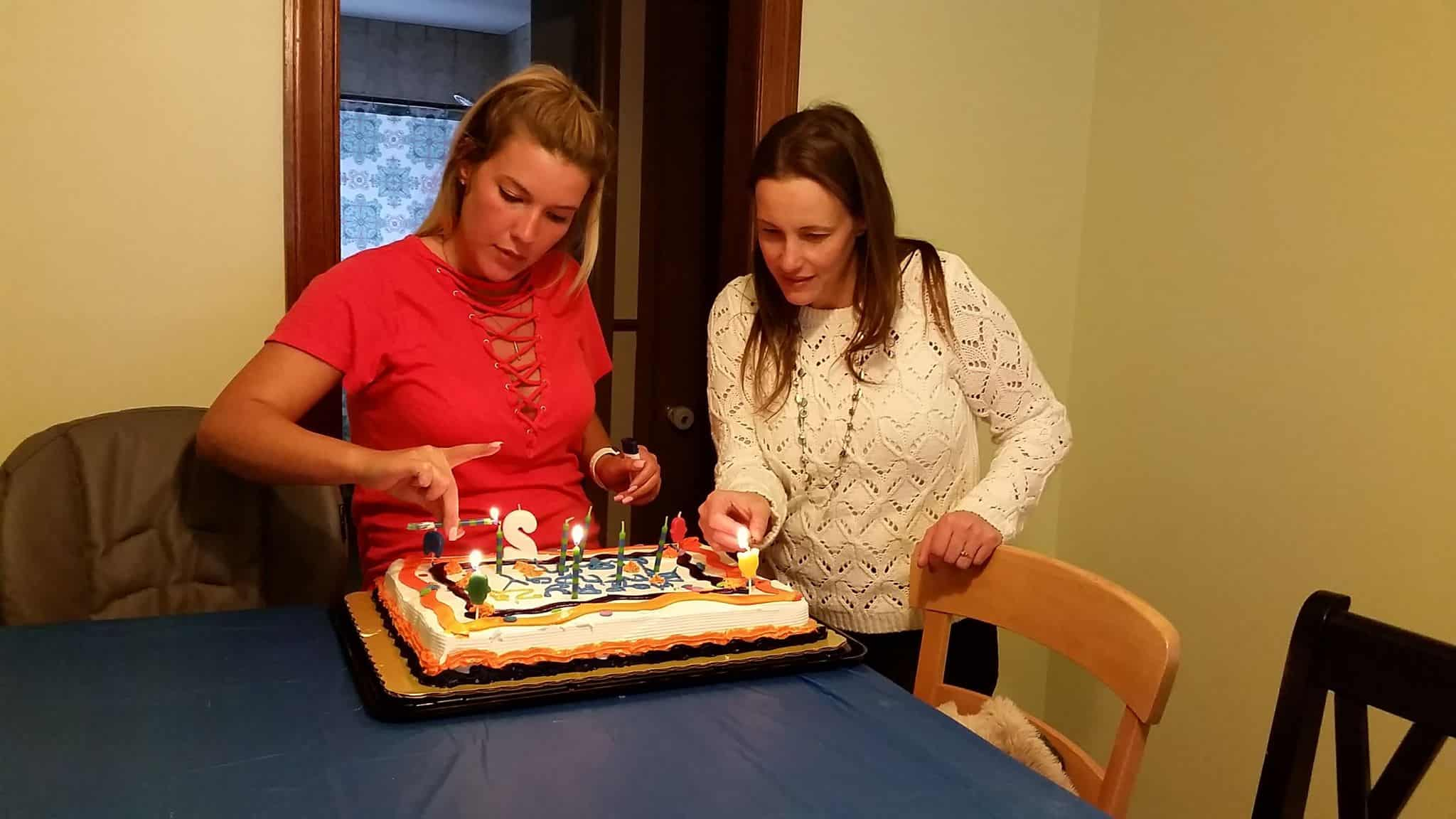 A small group of women surrounding a birthday cake.