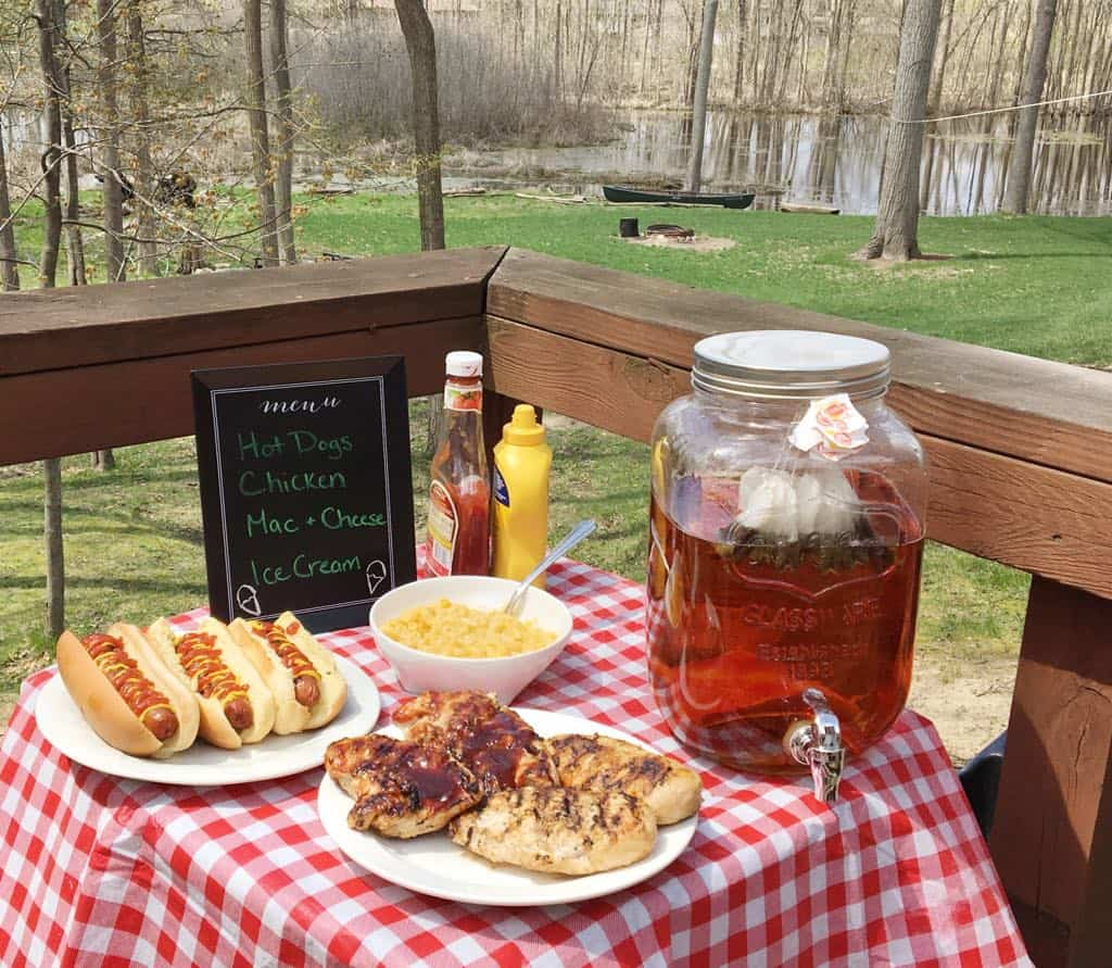 An outdoor picnic with chili dogs, sweet tea, and more delicious foods.