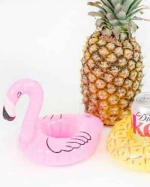 flamingo drink floatie holder sitting on a table with a can of soda and a pineapple