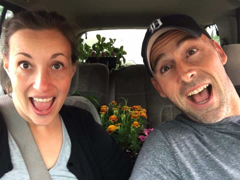 A man and a woman smiling for the camera with flowers in the back seat.