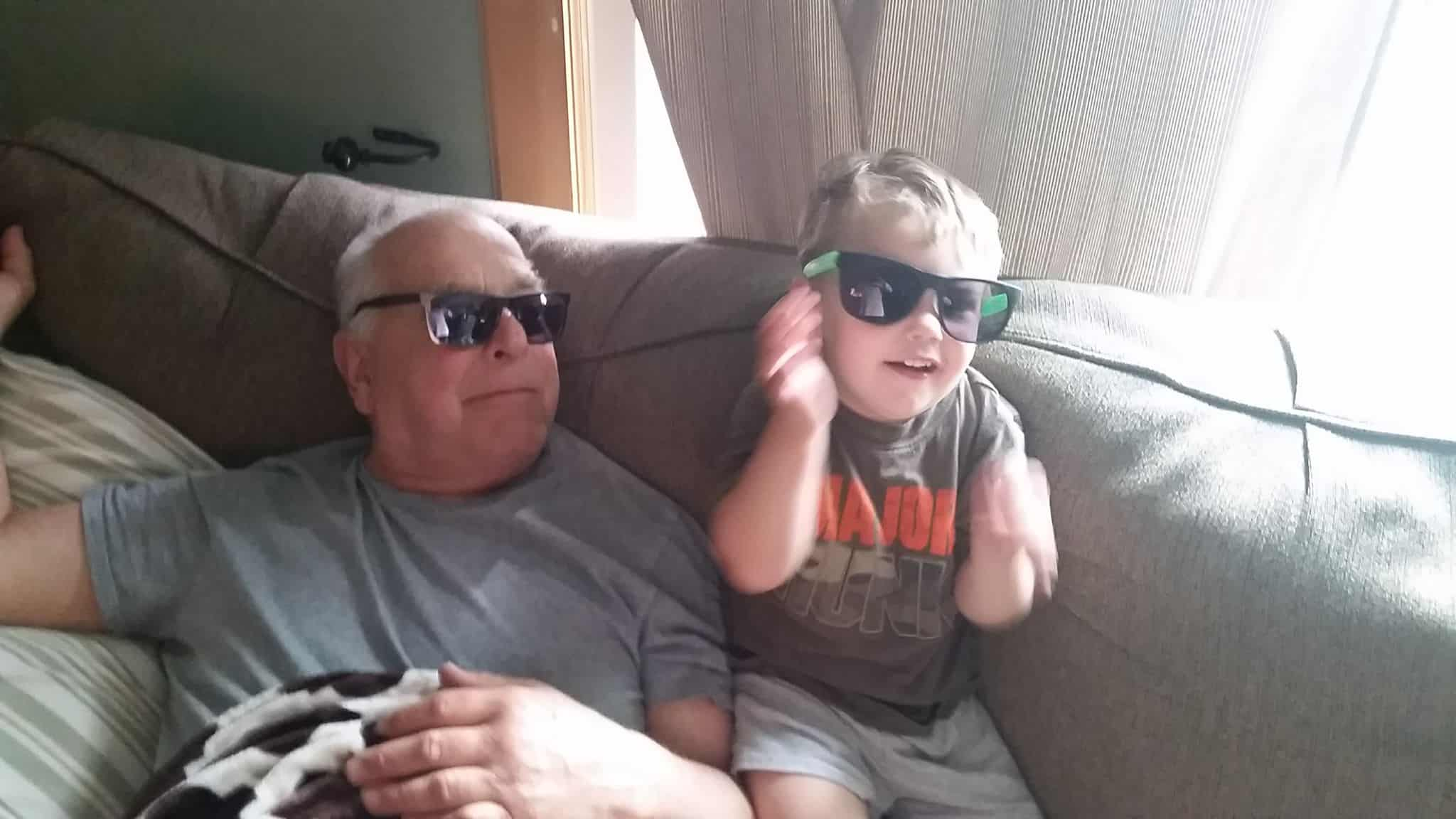 Grandson and great-grandfather wearing matching sunglasses and smiling together.