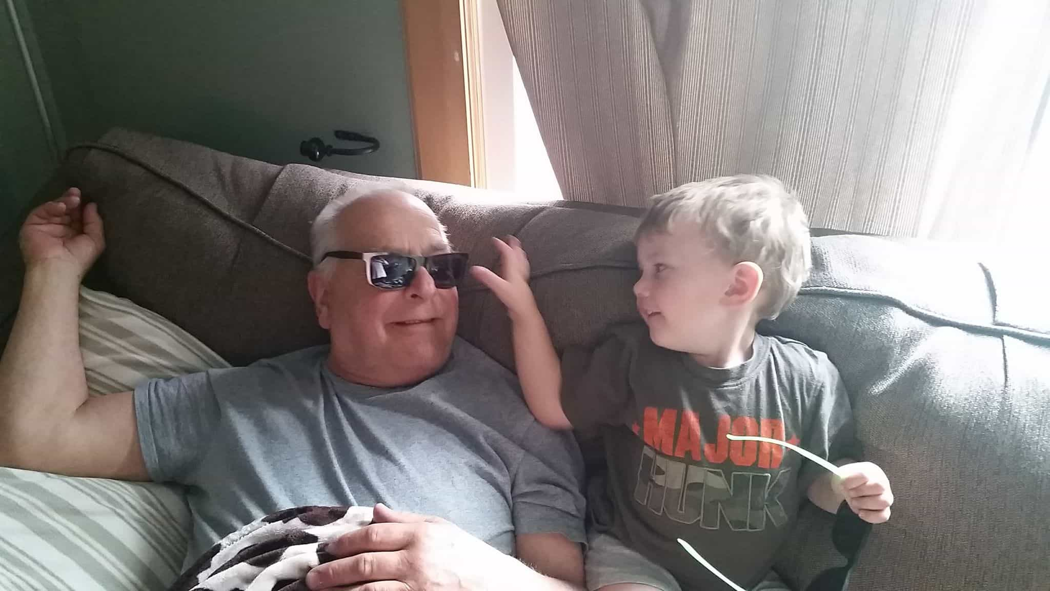 Grandpa sitting next to grandson. Both are smiling and having fun.