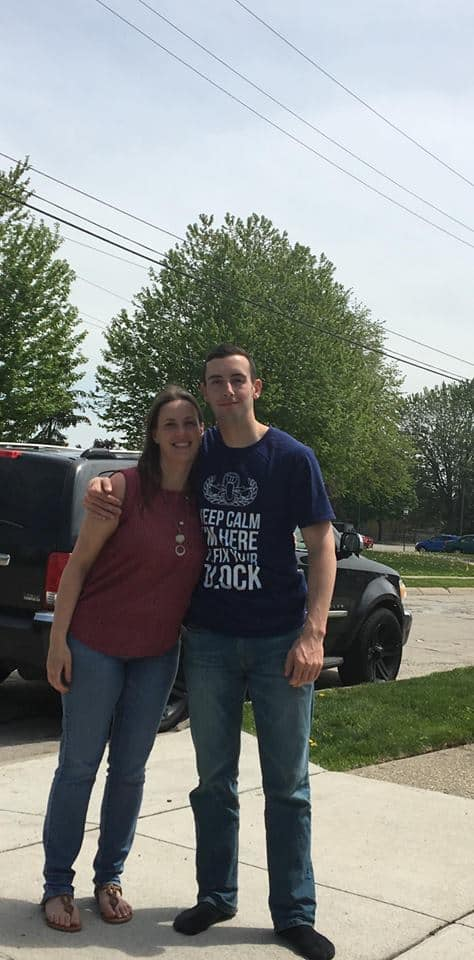 A man and a woman standing in a parking lot