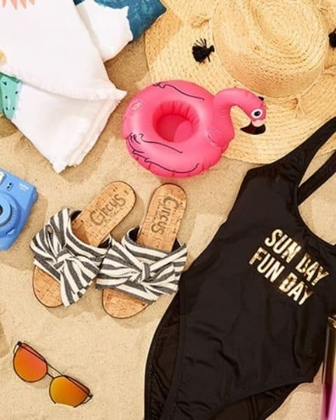Flatlay image of a swimsuit, sandals, sunglasses and a towel