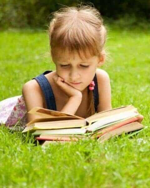 Child reading a stack of books in the grass.