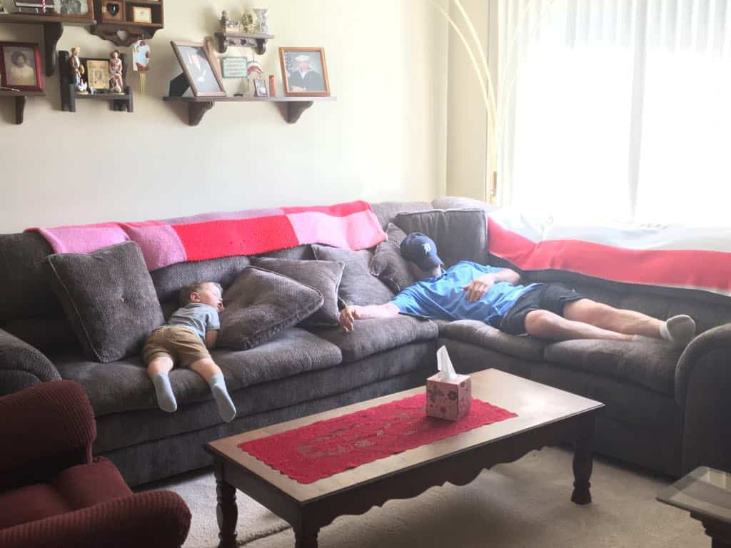 A grandfather and grandson napping on the couch.