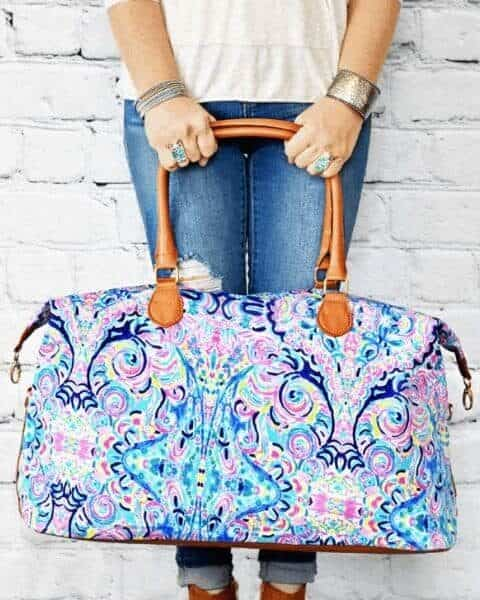 woman holding a paisley weekender bag while standing against a white brick wall