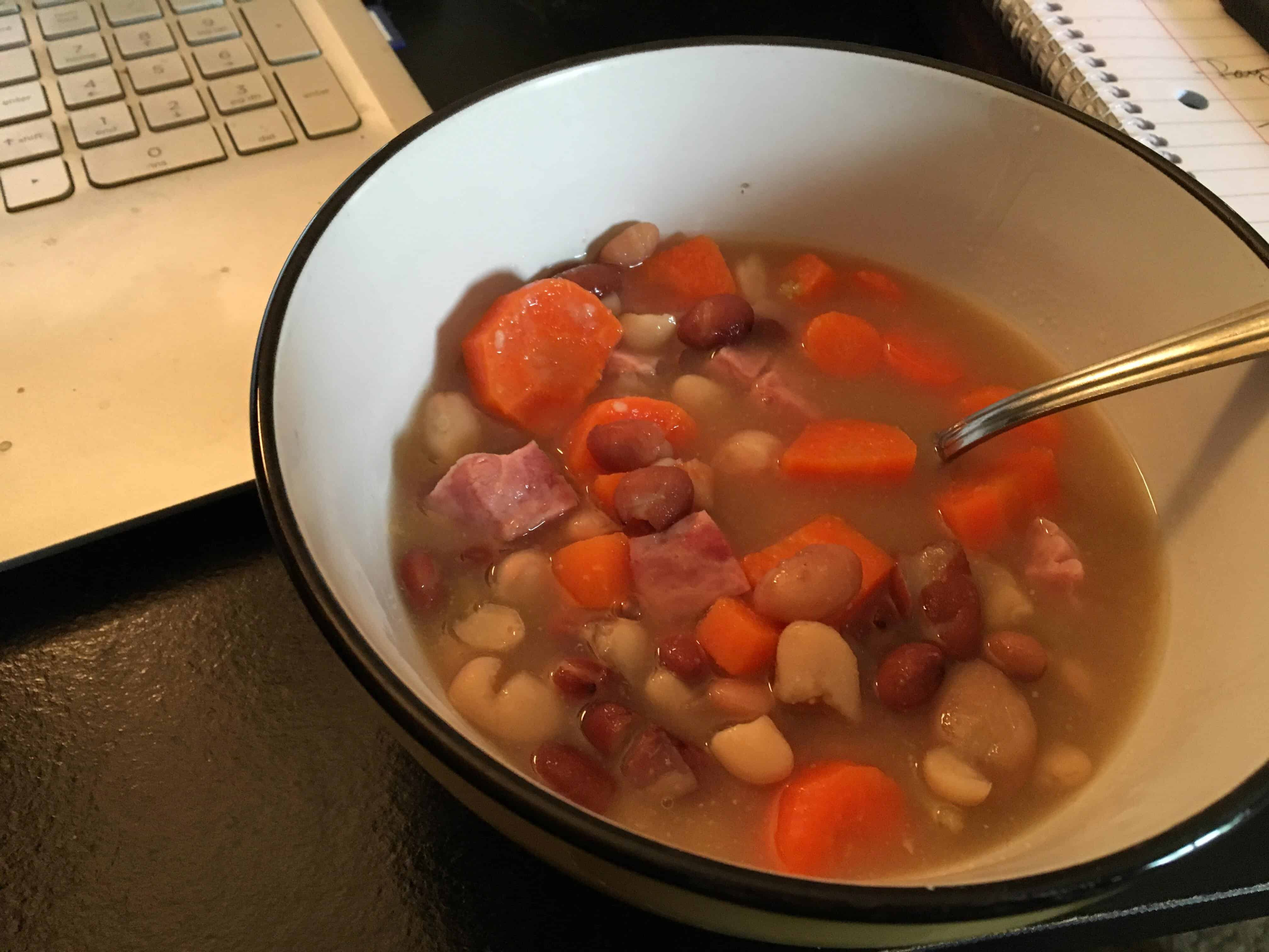 A bowl of soup and a spoon, with Bean and Recipes