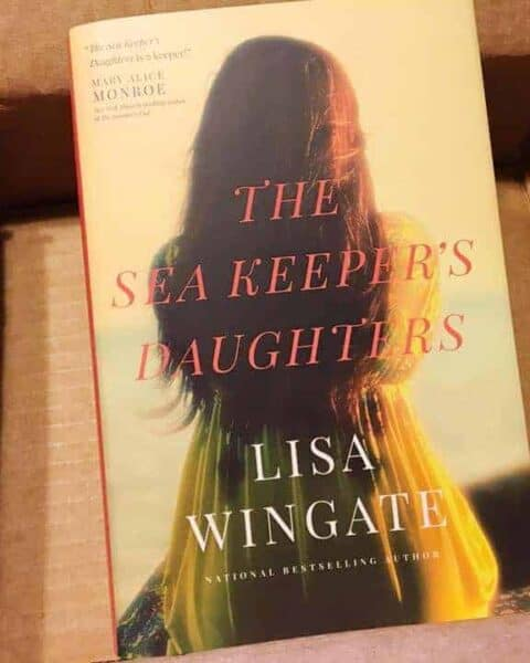 A book sitting on top of a table. The Sea Keeper's Daughters by Lisa Wingate.