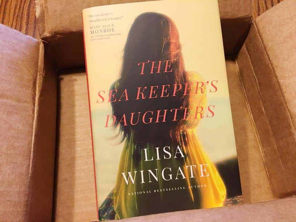 A book sitting on top of a table. The Sea Keeper\'s Daughters by Lisa Wingate.