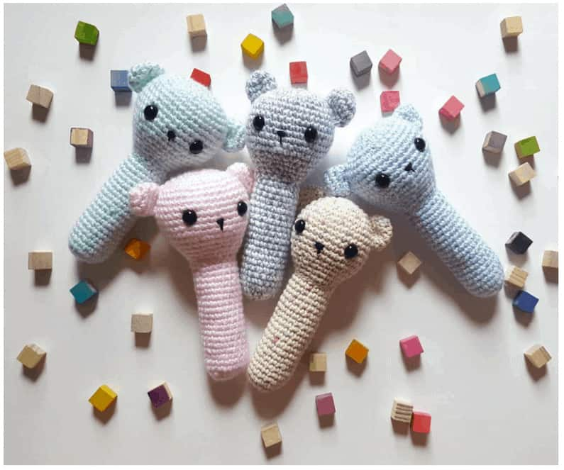 Blue and pink crochet baby rattles with little black eyes.