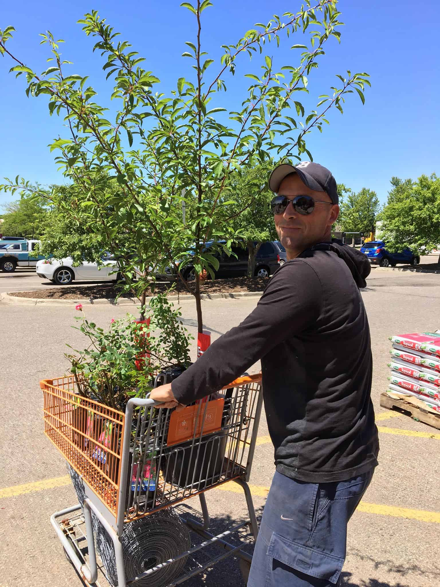 A man with a grocery cart of plants.