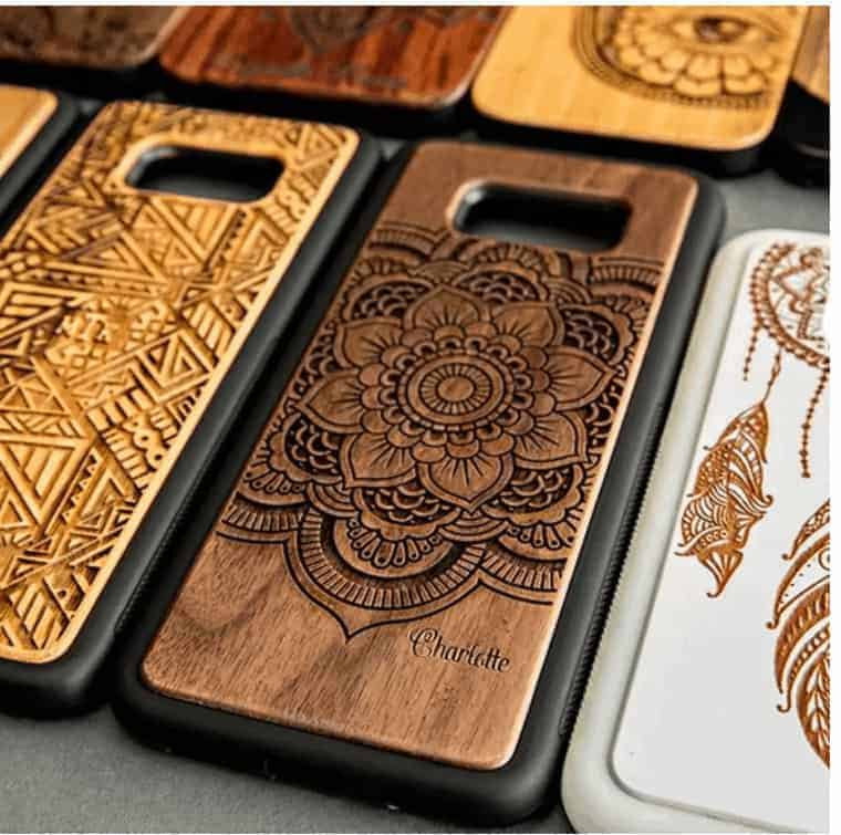 several wooden phone cases that are engraves with designs