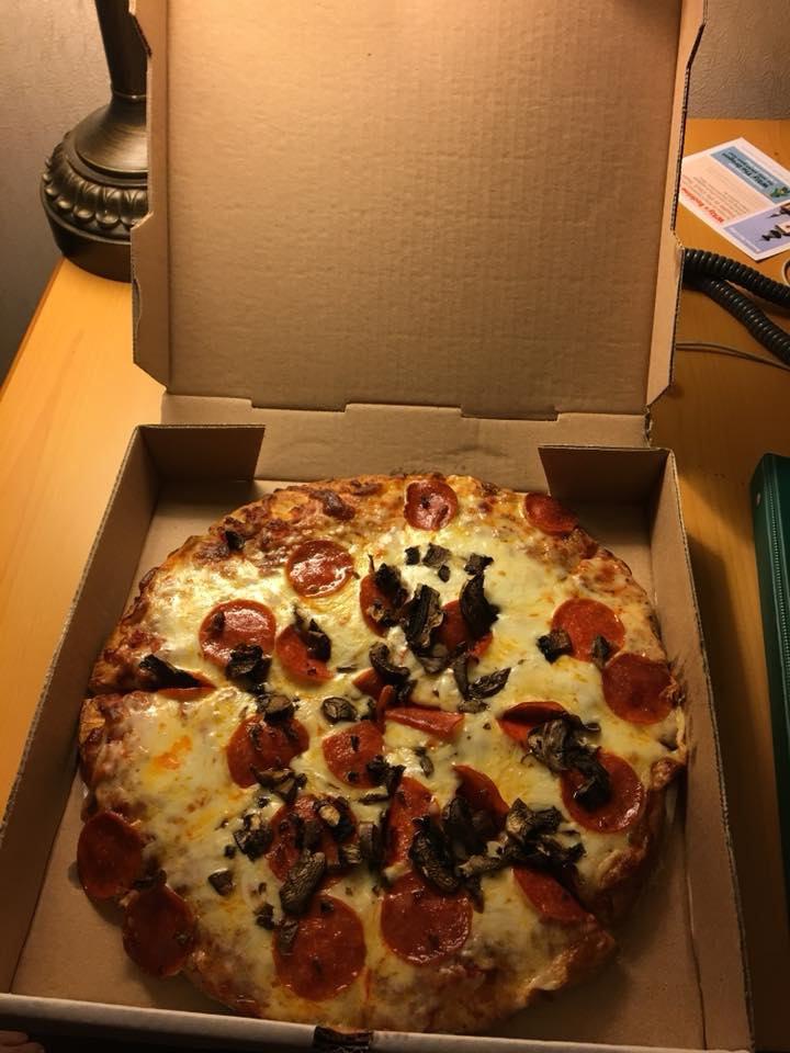 A pizza sitting on top of a box. The Bavarian Inn Summertime Edition