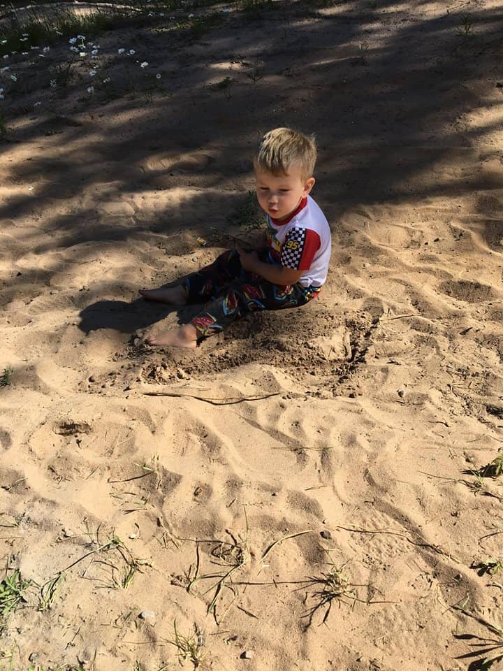 A little boy that is sitting in the sand